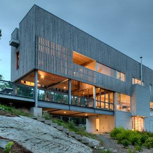Esempio della facciata di una casa moderna a tre piani con rivestimento in legno e tetto piano