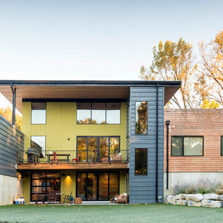 Diseño de fachada amarilla, actual, grande, de dos plantas, con tejado plano y revestimientos combinados
