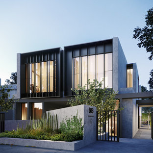 Large contemporary three-storey stucco grey townhouse exterior in Melbourne with a flat roof and a metal roof.