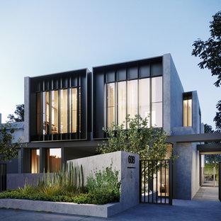 Modelo de fachada de casa pareada gris, actual, grande, de tres plantas, con revestimiento de estuco, tejado plano y tejado de metal