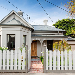 Inspiration for a small victorian one-storey concrete grey house exterior in Melbourne with a gable roof and a metal roof.