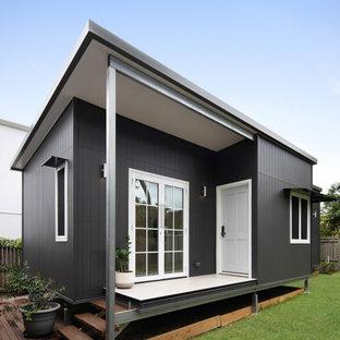 Foto på ett litet funkis hus, med platt tak och tak i metall