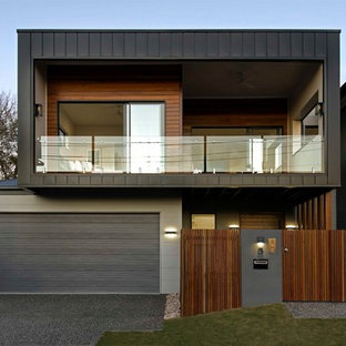 Inspiration for a contemporary two-storey black exterior in Brisbane with mixed siding and a flat roof.