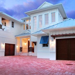Réalisation d'une très grand façade de maison blanche marine à un étage avec un revêtement en stuc et un toit à quatre pans.