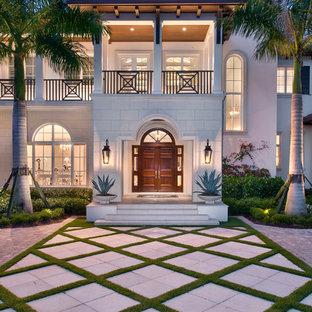 Exotisk inredning av ett mycket stort beige hus, med två våningar och blandad fasad