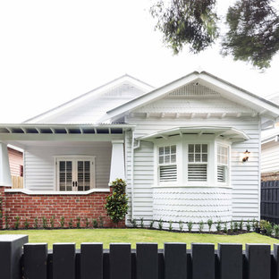 Example of an eclectic white one-story mixed siding gable roof design in Melbourne with a metal roof