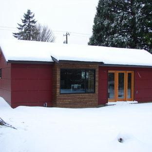 Foto de fachada roja, moderna, pequeña, de una planta, con revestimiento de aglomerado de cemento y tejado a dos aguas
