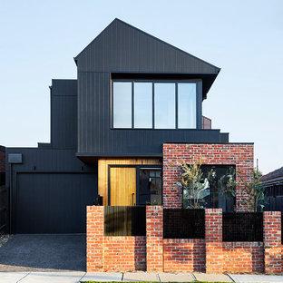 Mittelgroßes, Zweistöckiges, Schwarzes Modernes Einfamilienhaus mit Holzfassade, Satteldach und Blechdach in Melbourne