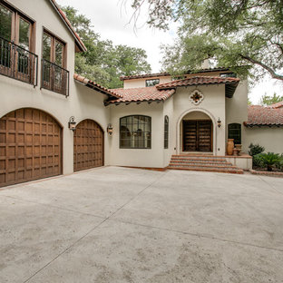 Large tuscan beige two-story stucco exterior home photo in Dallas