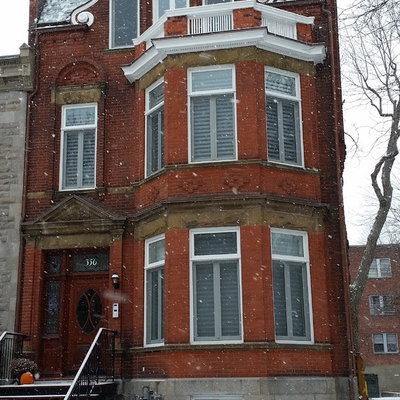 Inspiration for a large timeless red three-story brick gable roof remodel in Montreal