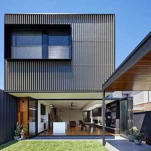 This is an example of a contemporary two-storey grey house exterior in Melbourne with metal siding and a flat roof.