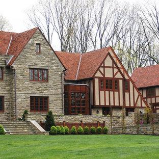Стильный дизайн: дом в классическом стиле с облицовкой из камня и красной крышей - последний тренд