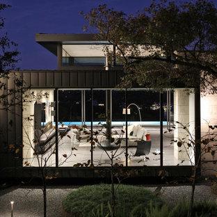 Imagen de fachada de casa negra, contemporánea, grande, de dos plantas, con revestimiento de metal, tejado plano y tejado de metal