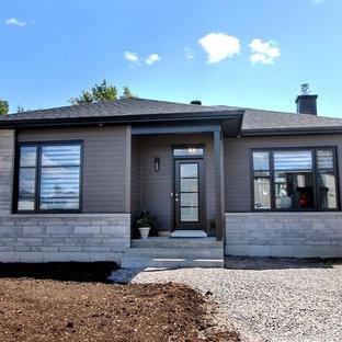 モントリオールのコンテンポラリースタイルのおしゃれな家の外観 (混合材サイディング、茶色い外壁、半切妻屋根、戸建、板屋根) の写真