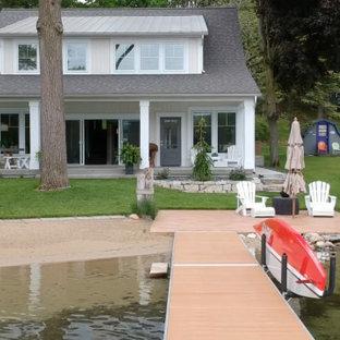 Cette image montre une façade de maison beige rustique de taille moyenne et à niveaux décalés avec un revêtement en vinyle, un toit à deux pans et un toit mixte.