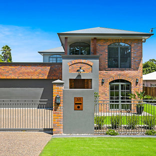 Design ideas for a large industrial two-storey brick multi-coloured house exterior in Other with a gable roof.
