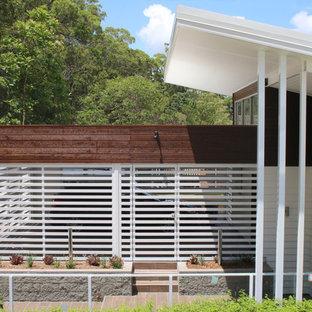 Imagen de fachada de casa blanca, costera, grande, de tres plantas, con revestimiento de aglomerado de cemento, tejado plano y tejado de metal