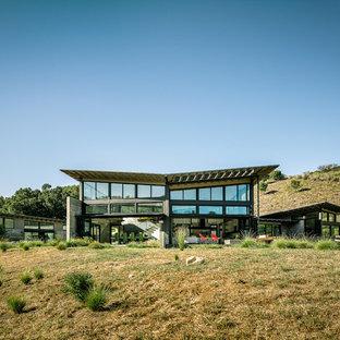 Aménagement d'une grand façade de maison contemporaine de plain-pied avec un toit papillon.
