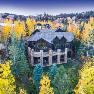 Huge mountain style brown two-story stone house exterior photo in Denver with a hip roof and a shingle roof