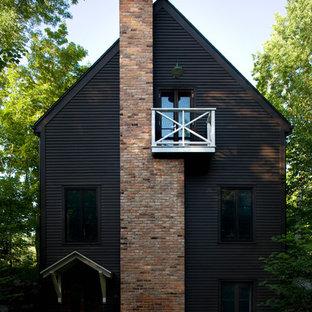 Immagine della facciata di una casa nera scandinava a due piani