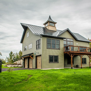 Example of a mid-sized eclectic green two-story wood exterior home design in Manchester with a metal roof