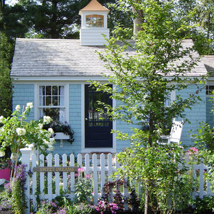 Small cottage chic blue one-story wood exterior home photo in Tampa with a shed roof
