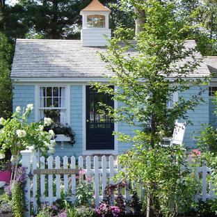 Diseño de fachada azul, romántica, pequeña, de una planta, con revestimiento de madera y tejado de un solo tendido