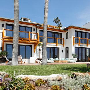 Diseño de fachada de casa blanca, marinera, grande, a niveles, con revestimiento de estuco y tejado de metal