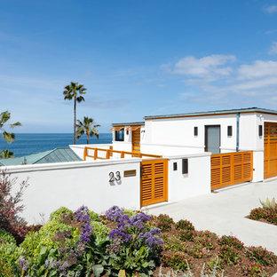Foto de fachada de casa blanca, marinera, grande, a niveles, con revestimiento de estuco y tejado de metal