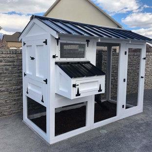 Modelo de fachada blanca, campestre, pequeña, con revestimiento de madera, tejado a dos aguas y tejado de metal