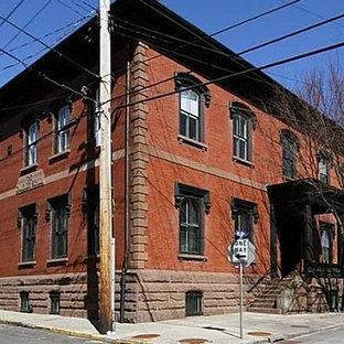 Inspiration for a large industrial red three-story brick exterior home remodel in New York with a mixed material roof