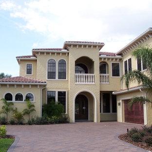 Diseño de fachada amarilla, mediterránea, grande, de dos plantas, con revestimiento de estuco y tejado a cuatro aguas