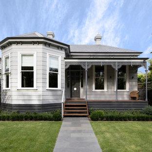 На фото: большой, одноэтажный, деревянный, серый частный загородный дом в викторианском стиле с вальмовой крышей и крышей из гибкой черепицы с