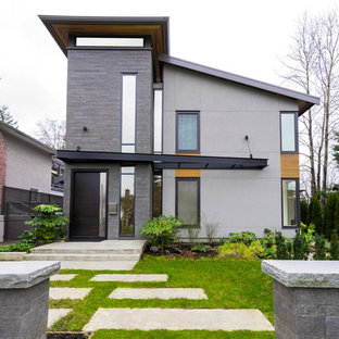 Mid-sized minimalist gray three-story mixed siding house exterior photo in Vancouver with a shed roof