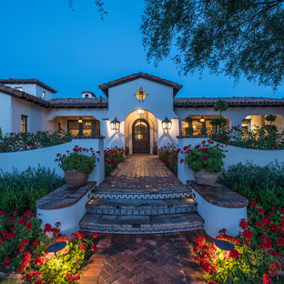 Inspiration for a large mediterranean white one-story stucco exterior home remodel in Phoenix with a shingle roof