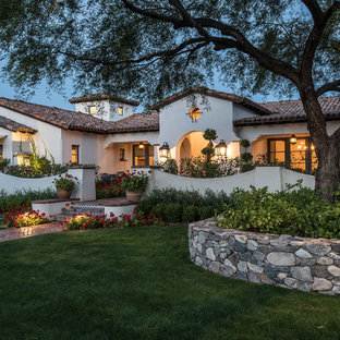 Inspiration for a large mediterranean white one-story stucco exterior home remodel in Phoenix with a tile roof