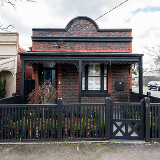 This is an example of an eclectic one-storey brick red house exterior in Melbourne.
