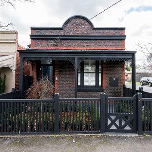 Foto de fachada de casa roja, bohemia, de una planta, con revestimiento de ladrillo