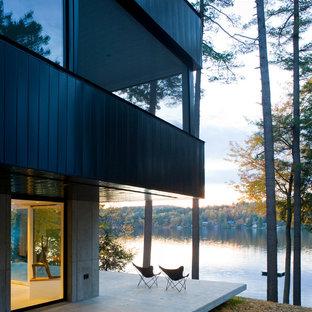 Idéer för stora funkis svarta hus, med metallfasad, två våningar, platt tak och tak i metall