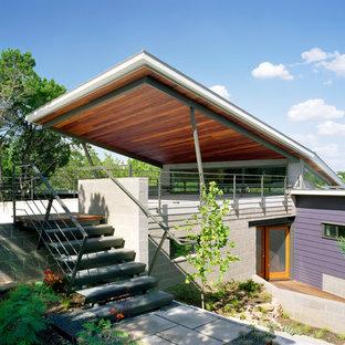 Foto på ett stort funkis lila hus, med två våningar, platt tak och blandad fasad