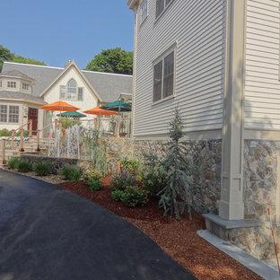 Foto de fachada de casa beige, costera, de tamaño medio, de tres plantas, con revestimiento de piedra, tejado a dos aguas y tejado de teja de barro