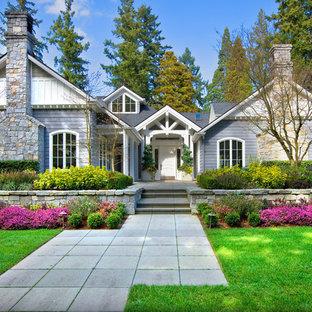 Immagine della facciata di una casa viola classica con rivestimento in pietra e tetto a capanna