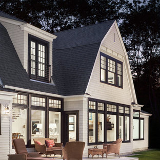 Foto de fachada blanca, marinera, de dos plantas, con revestimiento de madera y tejado a doble faldón