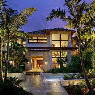Idée de décoration pour une grand façade de maison beige ethnique à un étage avec un toit à quatre pans et un toit en shingle.
