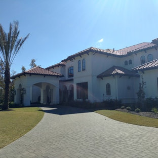 Inspiration for a huge mediterranean white two-story stucco house exterior remodel in Houston with a tile roof