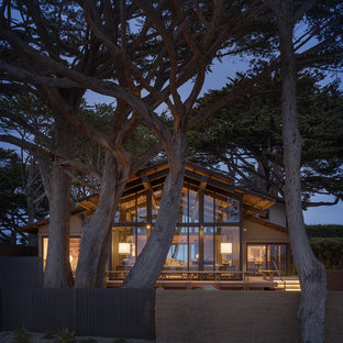 Example of a beach style beige one-story glass exterior home design in Other