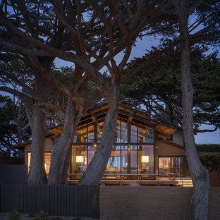 Пример оригинального дизайна: одноэтажный, стеклянный, бежевый частный загородный дом в морском стиле с двускатной крышей