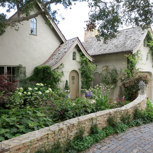 Example Of A Large Cottage Chic Beige Two Story Adobe Gable Roof Design In San