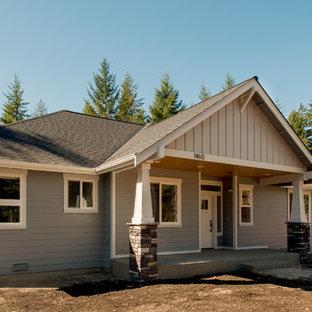 Foto della facciata di una casa unifamiliare grigia american style a un piano di medie dimensioni con rivestimento in vinile, tetto a capanna e copertura a scandole