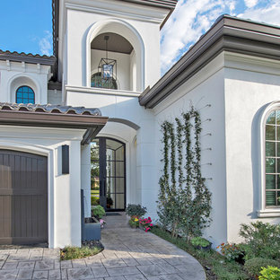 Design ideas for a large mediterranean two-storey stucco white house exterior in Tampa with a hip roof and a tile roof.
